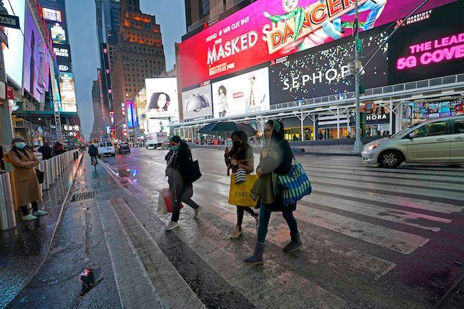 Άνθρωποι που βγήκαν για ψώνια περπατούν σε έναν σχεδόν άδειο δρόμο την Παραμονή των Χριστουγέννων, στη Νέα Υόρκη, 24 Δεκεμβρίου 2020.